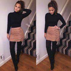 Black turtleneck, skirt, black tights, black boots, pony tail