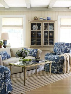 Say Hello to Florals Soften the lines of cottage architectural staples, such as paneled walls and exposed ceiling beams, with a swirly floral print. Taking its color cues from a collection of vintage earthenware jugs, a royal blue motif brings the two plush armchairs in this living room into bloom. Kick-pleat skirting on the chairs adds to the furnishings' feminine appeal, while a striped rug underfoot keeps the room from looking too sweet.