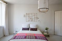 On the bed is the Hay Plus 9 Throw. On the wall is artwork from Corinne Gilbert's former store MC & Co. and the Menu Tribeca Staple Wall Lamp. The pendant light is the Ay Illuminate Z2 Ona White Lamp.