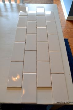 DIY tile backsplash- Considering doing this behind the stove and at .22 cents a piece why not?!