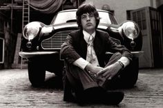 Posing in front of an Aston Martin DB6, Mick Jagger is captured in a black & white photo in Central London.