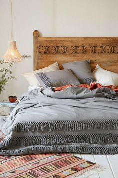 Bed on floor with bohemian decor and intricate wood headboard.