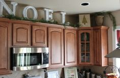 Big letters and pine garland above the kitchen cabinets by sara