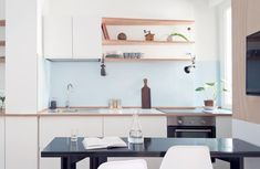 This small apartment kitchen has a light blue backsplash and white cabinets to keep it bright. Small Apartment Kitchen, Decor, Custom Wall Unit, Small Kitchen Layouts, Apartment, Small Apartments, Living Design, Home Decor, Tiny Living
