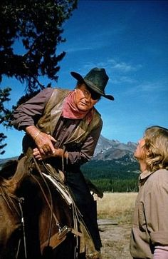 ROOSTER COGBURN - John Wayne visits with a crew member while horseback - Sequel to the Charles Portis novel 'True Grit' - A Hal Wallis Production - Paramount