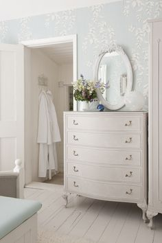 I like this chest of drawers and mirror and simple decor and I see the white bathrobe in the room next door.  Neat and tidy.  Like that.