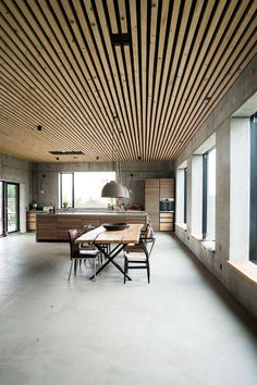 This beautiful and spacious dining room combines different materials like concrete and tree. This big house is made out of concrete is located on a small island in Denmark.