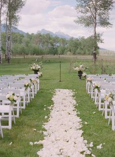 White rose flower petals line the ceremony aisle.  Snake River Ranch wedding near Jackson Hole, Wyoming. Photo by Carrie Patterson.
