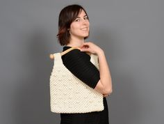 ($31.00) This vintage handbag by Mister Ernest is functional and stylish. This bag features an off white macrame design and wooden handles. This bag has a snap closure and an inside pocket for added convenience. This bag is in excellent vintage condition.