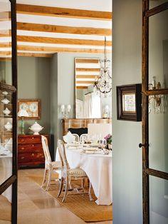 Comedor con paredes en color verde agua, chimenea y lámpara de araña. Verde agua: bienestar