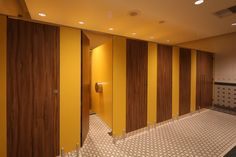 Marcato toilet cubicles, manufactured from solid grade laminate, with wood veneer doors complemented by yellow partitions.