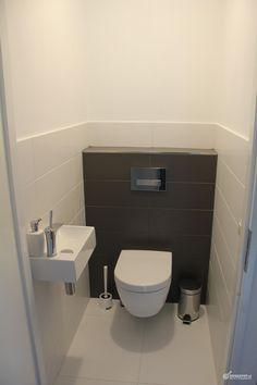 Lichte wand en vloertegels met toilet achterwand van antraciete wandtegels