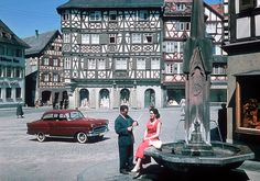 Vintage Opel photo 1957 Opel Olympia Rekord  I'm not sure about the location of this photo, but I have a feeling it could be Rothenburg ob der Tauber. This is  a 1957 Opel Olympia Rekord, so this photo is probably used for the 1958 calander. Please note how the car and the lady's dress are about the only items with real color here. The fountain doesn't look to be in a very fine shape too.