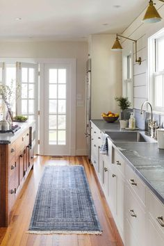 """Classic Galley Kitchen - Tour This Stunning Waterfront Farmhouse - Southernliving. In the kitchen, the designer paid tribute to Fishing Bay's sailing tradition – and the family's own love of the watersport – with classic white shiplap and nautical-inspired Visual Comfort sconces. """"Eliminating hanging cabinets near the sink made more room to harness the view of the local sailing school from the kitchen windows,"""" says Molster. """"We also limited the hanging fixtures to the antiqued brass…"""