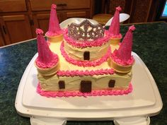 This is Josie's castle cake. For her 3rd birthday. It was really pretty easy to make. I just followed directions I found here on Pinterest for a similar cake. The bottom is just a 13x9, with a round cake on top. The turrets are just sugar cones iced and rolled is the sparky sugar. They rest on the bottom half of a regular ice cream cone. And a tiara on top.:) I used Hershey bar pieces for the windows and drawbridge.