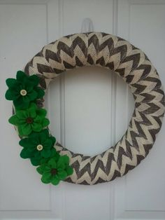 This wreath measures 14 in diameter and is (gray/cream) chevron burlap wrapped on a wreath form. It is decorated with handmade felt flowers