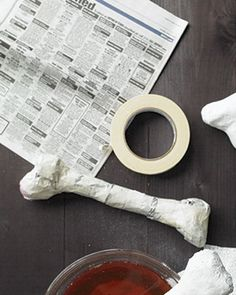 Newspaper, Masking tape, 4 tea bags, Rigid Wrap plaster cloth, cut 6-inch strips, by Activa,   Wad up pieces of newspaper. Wrap  with masking tape in select places to reinforce  Make tea with tea bags and a gallon of water  Wet 1 piece of plaster cloth in a bowl of tea, which will give the bones an aged appearance. Remove cloth, squeeze it out by running it between your index and middle fingers. Starting at the end, smooth plaster piece over the bone.  Repeat until bone is entirely covered.