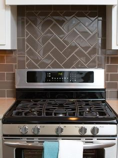 Glossy Finish - A glass subway tile backsplash takes a different pattern behind the stove than behind the countertops. Switching the pattern from basic to herring bone breaks up the solid-colored backsplash.