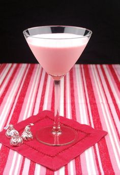 Pink chocolate martini....cheers!    Ingredients:    1 ounce vanilla vodka  1-1/2 ounces crème de cacao  1/2 ounce amaretto  1/2 ounce grenadine syrup  4 tablespoons Cool Whip  Ice  Directions:    Combine all ingredients in a shaker.  Shake until Cool Whip is completely dissolved.  Strain into a martini glass.