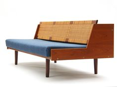 Sofa Daybed by Hans J. Wegner  Denmark  1950's  A convertible teak sofa daybed with a caned storage backrest, with an upholstered seat cushion. Manufactured by Getama.