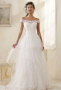 Brides: Modern Vintage by Alfred Angelo. Vintage off the shoulder soft a-line ball gown in re-embroidered lace and net. Delicately beaded lace covers the round neckline and natural waist bodice. Soft satin pleats highlight the waist, and the whimsical tiered net skirt flows into a chapel length train.