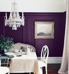 This dining room has been painted in a gorgeous shade of aubergine! Again we see it paired with white, white skirting, white ceiling, white dining room suite, even a white and crystal chandelier all make this purple dining room super hot!