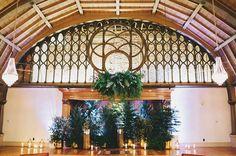 All greenery wedding backdrop with a fern chandelier