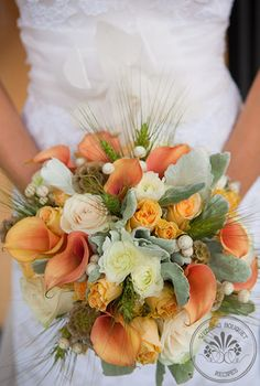 This Ranunculus and Wheat Grass fall inspired bouquet has peach and green tones in an elegant bouquet that would accent any bride.