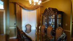 """Courtesy of InteriorDecorating.com  A pair of pinch pleated draperies mounted on a 2"""" wood pole with rings is accentuated by a pair of gorgeous finials. Swags with cascades complete this classic traditional look."""