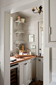 The adjacent butler's pantry was once a porch that held an old washer and dryer, but it's now an important extension of the kitchen. While the room has the same wood-plank walls, it also has a few distinctive differences: The brick floor is quaint and practical, a walnut countertop brings in a new surface with patina, and open shelving offers an attractive way to display bar items.