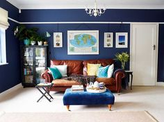 navy blue living room with tan leather sofa