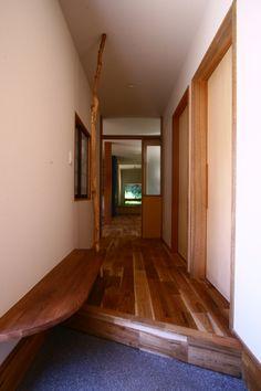 玄関に設けたベンチ。座るだけでなく、荷物を置いたりと何かと便利。 手摺りにもなる丸太は玄関の表情を全く変える、アクセント。