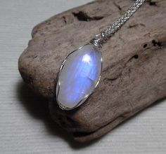 This One of a Kind necklace features a beautiful Genuine Moonstone Gemstone that has been wire wrapped with silver wire to create a pendant. The Moonstone itself is a oval shape that measures 16mm x 31mm and hangs off of an 18 chain. The chain is finished off with Genuine Opalite Gemstones at each end and a silver lobster clasp. This stone is so beautiful to look at and when the light hits it the right way, it glows blue! This necklace would make a lovely gift and will bring the wearer good…