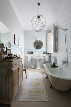 """I don't like it when bathrooms look too much like bathrooms,"" say Kayser. He removed the telltale tiling beneath the Greek-key trim, layering in books, vases, and various soaps and fragrances to build a comfortable rather than sterile atmosphere."