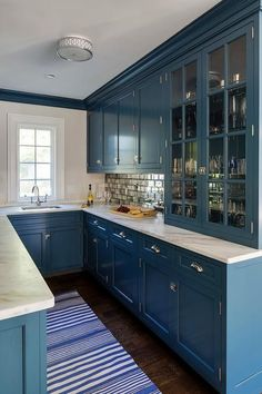 Stunning blue u-shped wet bar is lit by a nickel flush mount fixed over a blue striped rug accenting blue shaker cabinets accented with polished nickel vintage latch hardware and a honed gray and white marble countertop.