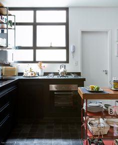 Cozinha industrial nos tons preto e branco. Carrinho serve como um apoio para louças e utensílios.