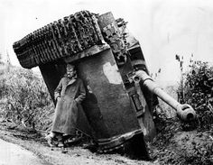 A British soldier hiding from the rain under an overturned German Tiger heavy tank in Italy, 1944.