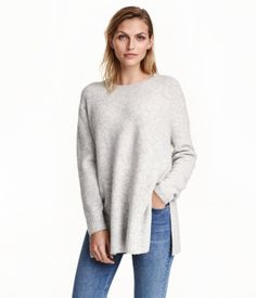 Light gray melange. Oversized sweater in a melange knit with wool content. Round neck, dropped shoulders, long sleeves, and slits at sides.