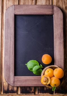 Fresh ripe apricots in wood bowl on vintage slate chalk board background. Selective focus. Background with place for some text. Top view by tanchy on @creativemarket