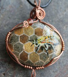 Each BLISS BLOSSOM is hand made with love & care & is one of a kind. Inspired by ancient treasure these elegant works of art are sure to dress up your day or night. Each copper blossom is hand hammered, antiqued & polished.  This one of a kind hand painted river stone shows a honey bee sitting on the honeycomb. Painting with very tiny brushes the bee is so realistic you can almost hear it buzzing. The pendant is wrapped in square antique copper wire & has 6 honey coloured Swarovski…