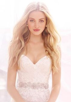 Ti Adora by Alvina Valenta 7457 is a romantically layered modified A-line bridal gown with a glamorous embroidered trim at the natural waist. It features a strapless sweetheart neckline with a draped English net overlay and hand placed re-embroidered lace throughout. This gown came from a designer bridal boutique and is in excellent condition. Ti Adora by Alvina Valenta 7457 is Ivory and a size 14.