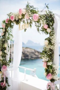 beautiful idea for your beach wedding. this romantic arch caressed by florals baby's breathe and tulle. via:weddingomania comments:walkingonsunshine:)