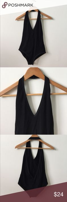 Black bodysuit with deep v neck and open back Black body suit. Medium. Deep v neck in front and open back. Brazilian cut bottom. Not see through. Goes around neck and has stretch. Button to close bottom Tops