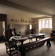 The Old Kitchen at Woolsthorpe Manor viewed from the door to the Wet Kitchen showing the Elizabethan oak table with richly carved baluster legs and a trestle form bench dating from around 1400
