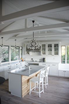 pickled wood floors, rustic wood on the island and country shaker cabinets are juxtaposed by a sparkly crystal chandelier for a shabby chic kitchen.