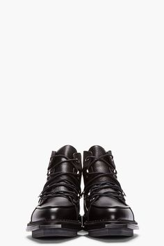 MCQ ALEXANDER MCQUEEN //  Black Leather Lace-up Lipp Boots  32114M047002  High-top leather boots in black with contrasting matte and textured finishes. Almond toe. Tonal lace up closure with gunmetal tone eyelets. Paneled upper. Squared welt at toe. Thick rubber foxing in black. Tonal stitching. Leather upper, rubber sole. Made in Italy.  $935 CAD