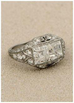 An antique Art Deco carré engagement ring with millegrain details and two 1.50 carat carré cut diamonds. Circa 1925.