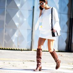 The mini dress moves from summer to fall with the chic addition of knee high #boots. Look for snakeskin styles as spotted at #MFW for added kudos. #streetstyle by @theurbanspotter