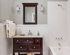 This master bathroom's white beadboard wainscoting under nude-colored upper wall make the warm tones of the wooden-framed vanity mirror and bathroom vanity cabinet pop.