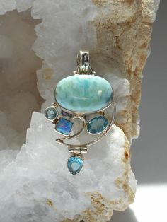 Amazing oval polished cabachon Caribbean Larimar gemstone accented with 3 brilliant faceted London Blue Topaz gemstones and 1 square Australian Fire Opal, set in 925-hallmarked sterling silver. Total
